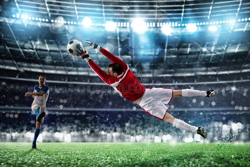 Goalkeeper catches the ball in the stadium during a football game. royalty free stock photography