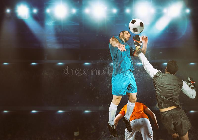 Goalkeeper catches the ball in the stadium during a football game royalty free stock photo