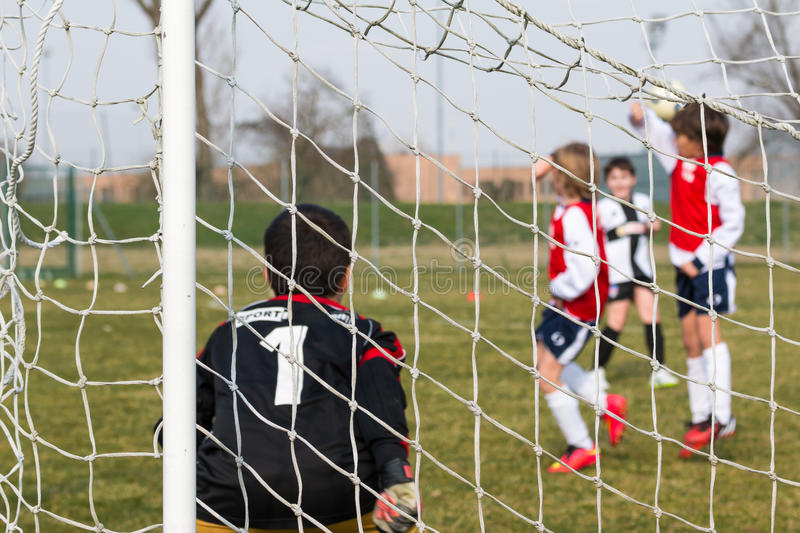 Goalkeeper, defenders on wall and little soccer player for a pen. Alty shot during match, behind view stock photos