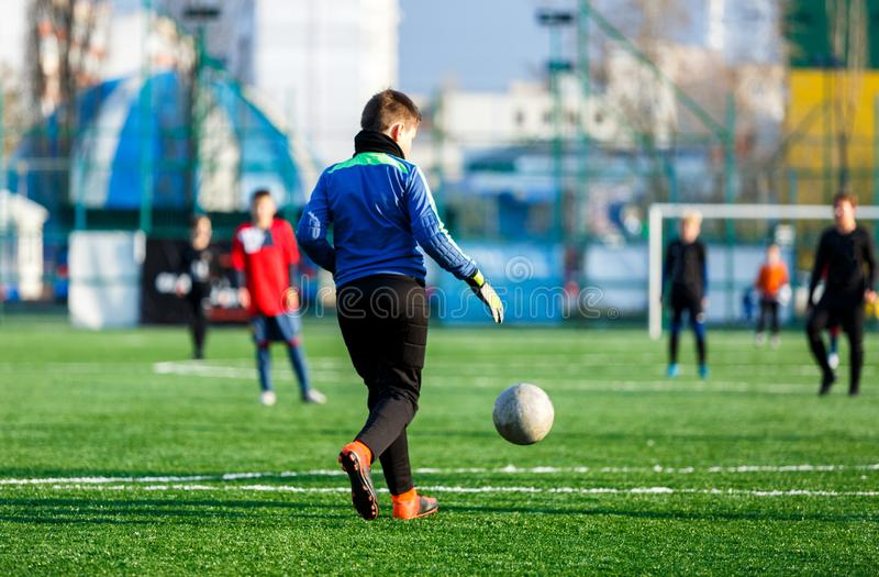Goalkeeper hits a ball on football field. Soccer game for kids, training, football, active lifestyle royalty free stock image