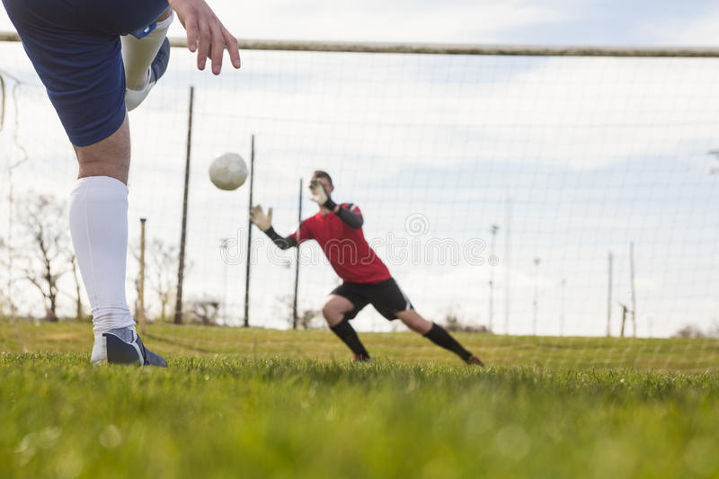 Goalkeeper in red saving a penalty. On a clear day royalty free stock images
