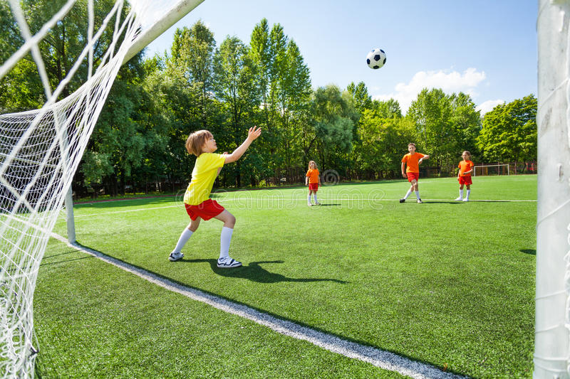 Goalkeeper tries to catch the football flying up stock photos