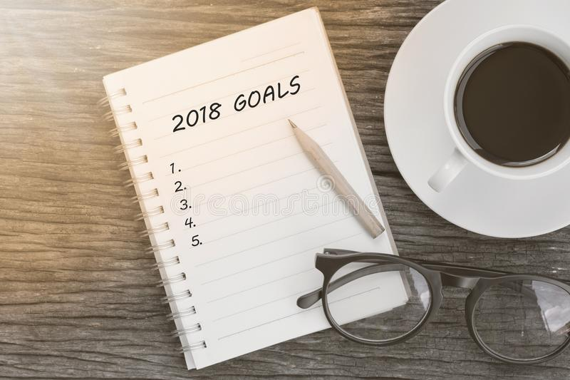 2018 Goals concept on notebook with glasses, pencil and coffee c royalty free stock photos
