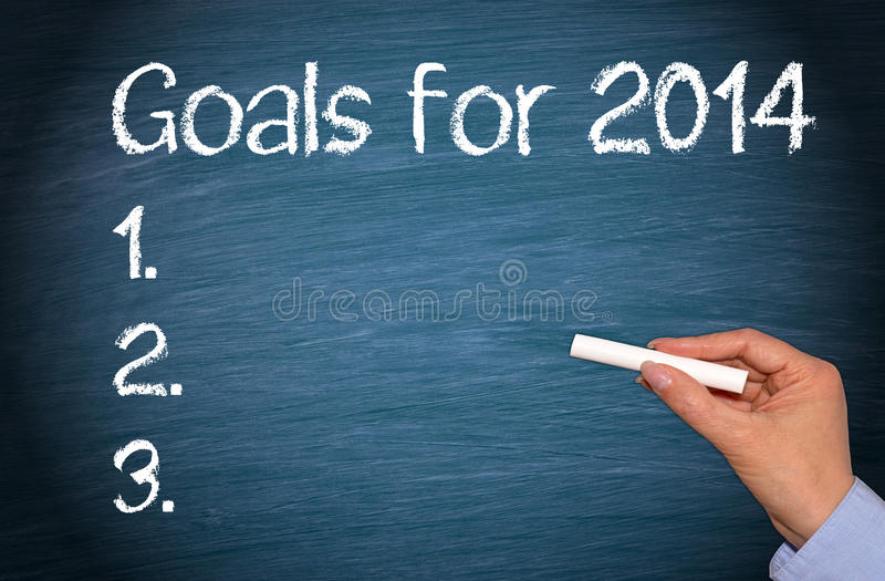 Goals for 2014. Hand of person writing goals for 2014 on blackboard or chalkboard stock image
