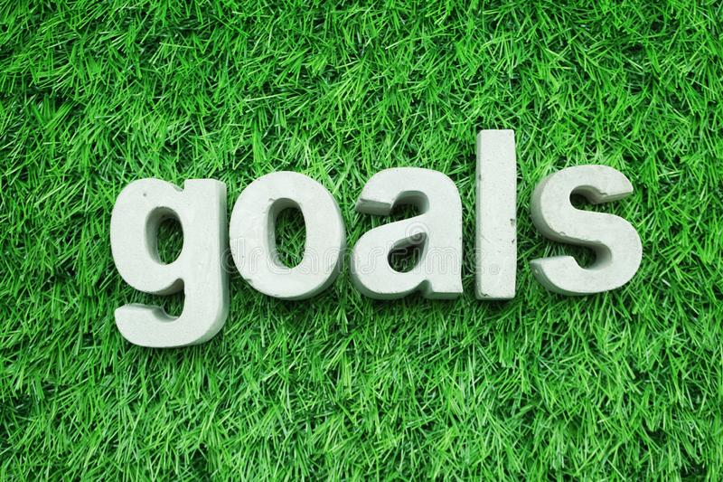 Goals made from concrete alphabet on green grass stock images