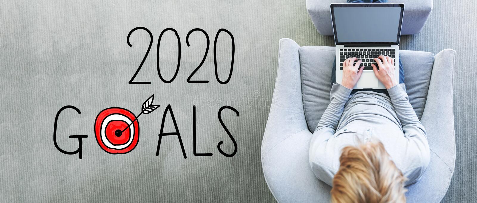 2020 Goals with man using a laptop. In a modern gray chair stock image