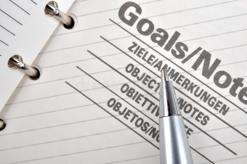 Goals and note. Goals plan or record in notepad and a sliver ball pen, shown as working goals, target, focus, objective important notes and other related stock photography