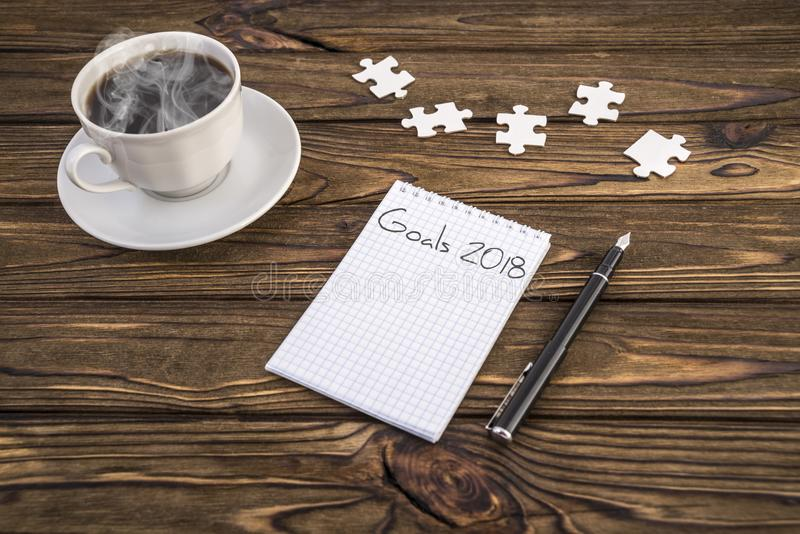 Goals 2018 on a notebook, pen, puzzles and coffee on a wooden table. stock image