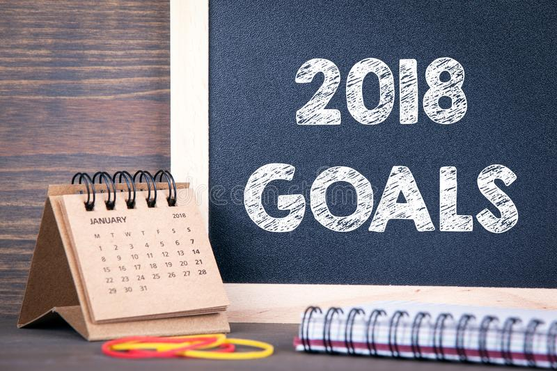2018 goals. paper calendar and chalkboard on a wooden table royalty free stock photo