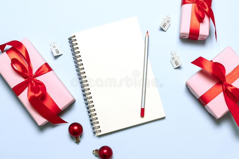 Goals plans dreams make to do list. New year winter holiday xmas concept writing in notebook with gifts and decor on blue royalty free stock image
