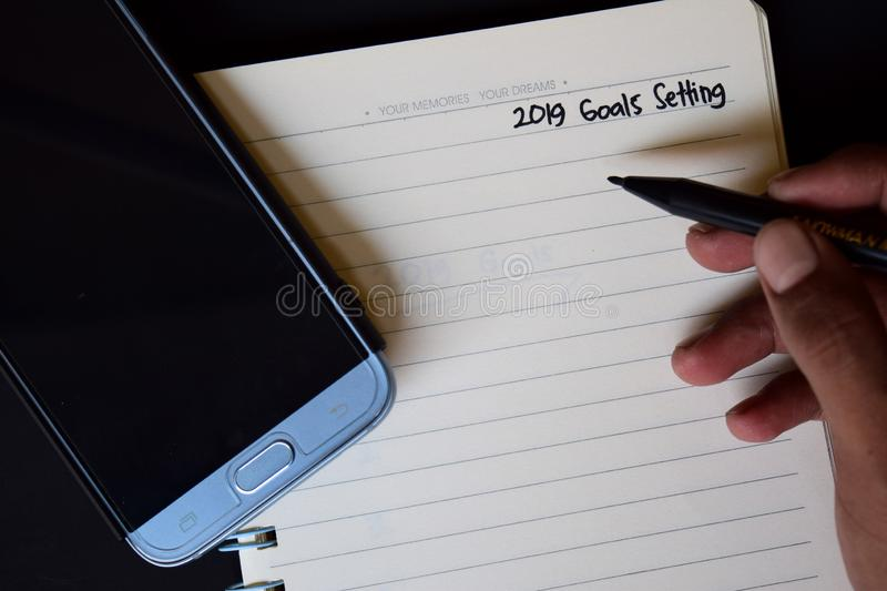 2019 Goals setting text in someone hand. Notebook, smartphone, compass and pen, with selective focus 2019 Goals setting text in someone hand with black royalty free stock photography