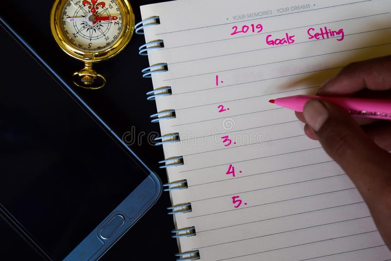 2019 Goals setting text in someone hand. Notebook, smartphone, compass and pen, with selective focus 2019 Goals setting text in someone hand with black royalty free stock photos