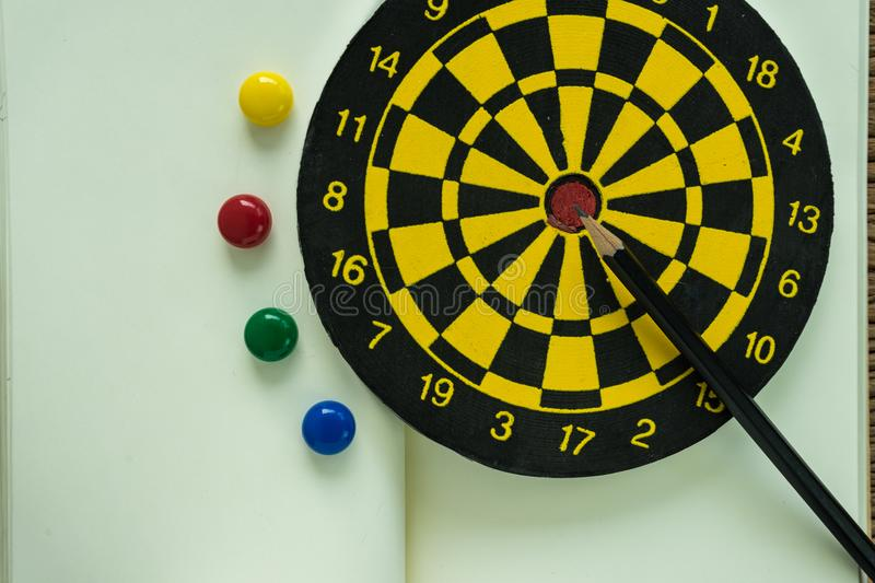 Goals or target concept with pencil on dartboard on white paper stock image