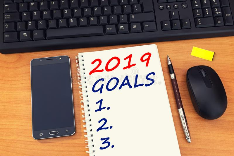 2019 goals text on notebook with office accessories, mobile phone and keyboard. Business plan, direction concepts stock photography