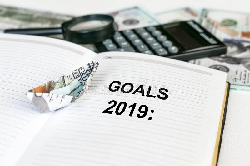 2019 goals text in open notebook with dollar banknote origami ship and calculator, money and magnifier in the background stock photo