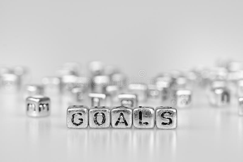 Goals word written on silver cube with black and white bokeh cu royalty free stock images
