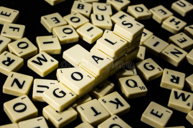 Goals word spelled with letter tiles in black background stock images
