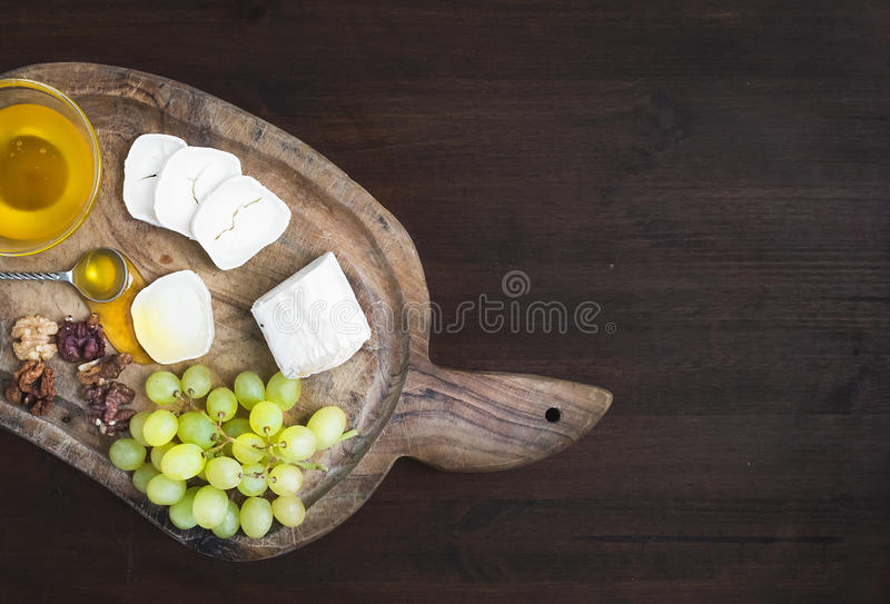 Goat brie cheese with fresh greapes, walnuts and honey on a rust stock photos
