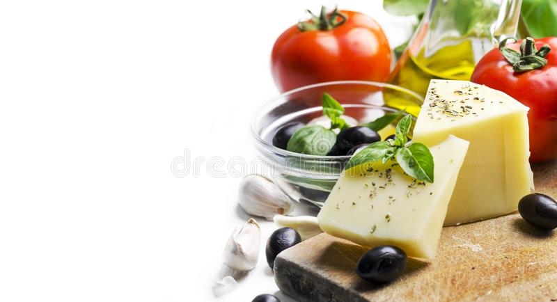 Goat cheese, olives, olive oil, tomato, garlic, basil and spices on wooden cutting board isolated on white background. Food royalty free stock photography