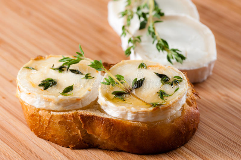 Goat cheese with thyme gratinated with honey. stock images