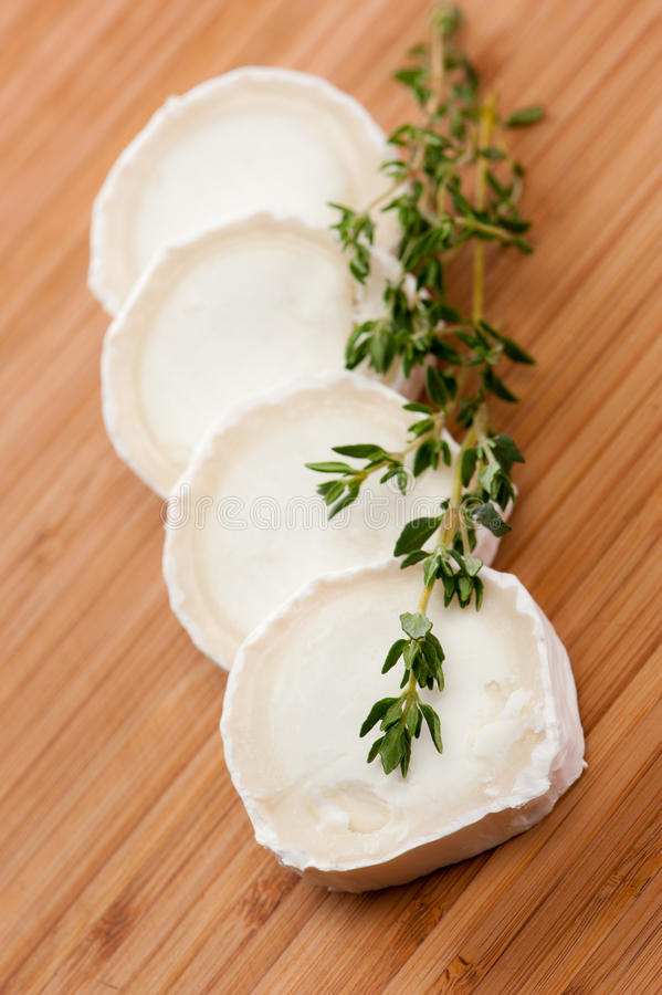Goat cheese with thyme on a wooden cutting board stock photography