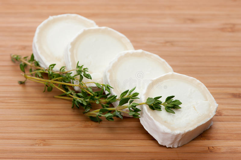Goat cheese with thyme on a wooden cutting board royalty free stock photography