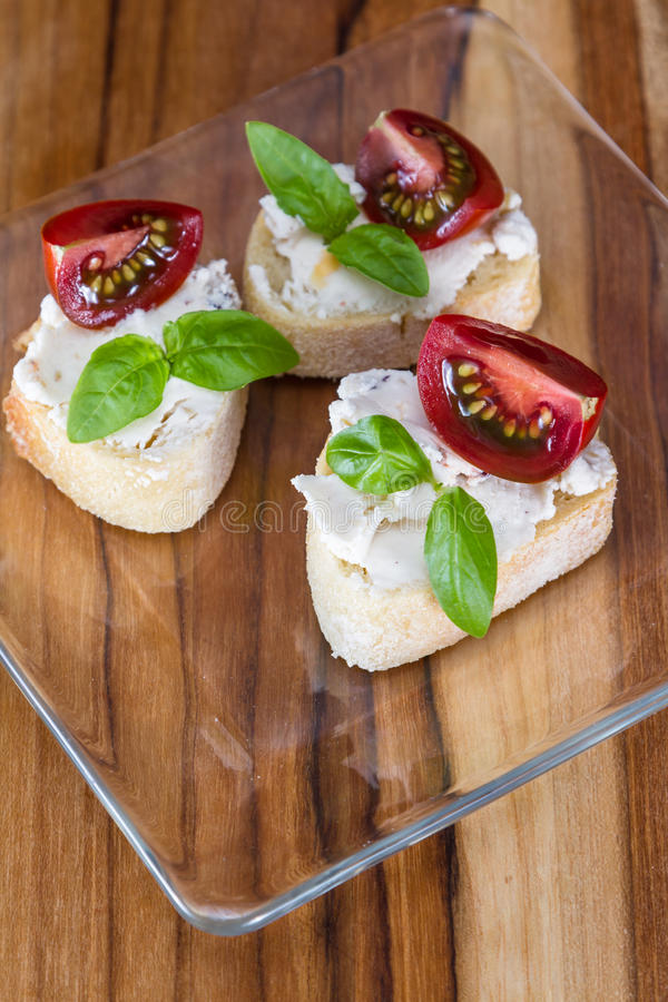 Goat cheese and tomato appetizer stock photography