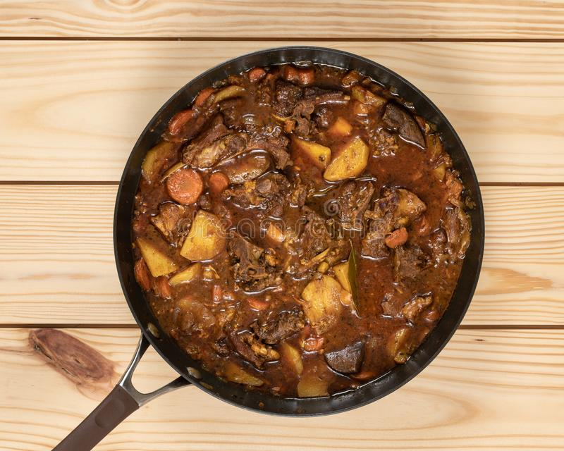 Goat Curry Stew. Close-up of colorful goat stew in cooking pan on top of wooden table stock images