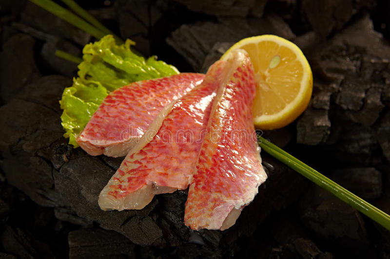 Goatfish fillets. A goat-fish (red mullet) fillets on coals ready for cooking with some herbs and a pies of lemon royalty free stock photos