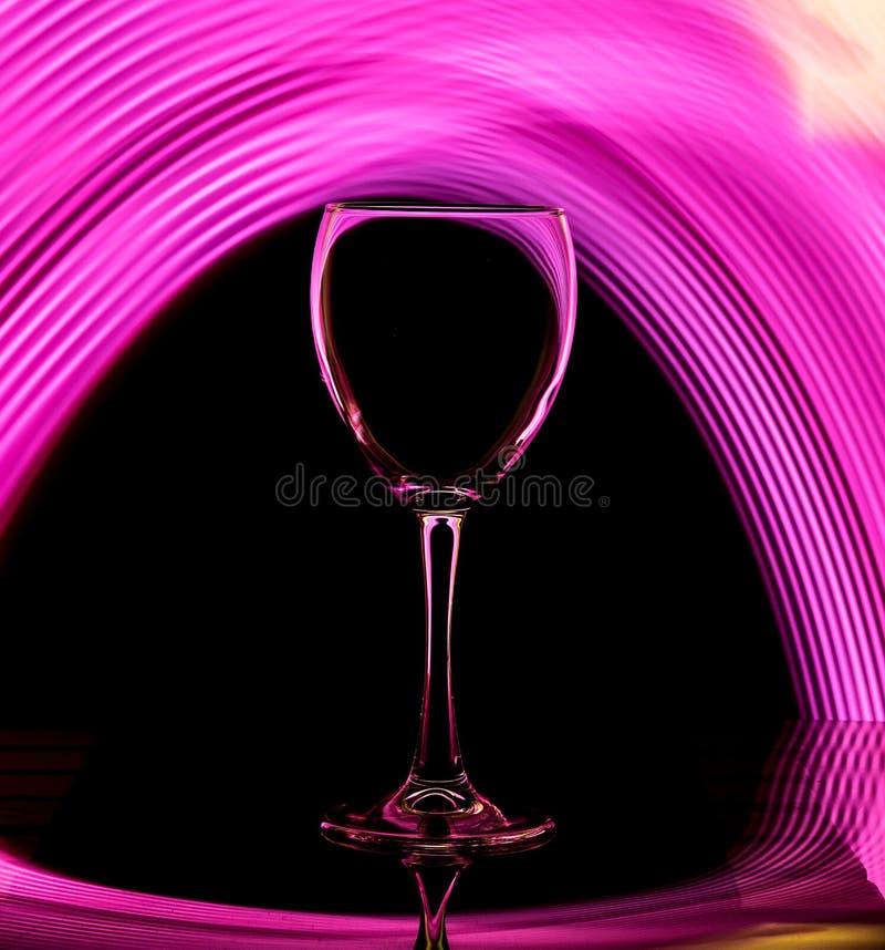 Gobelet en verre sur un fond noir avec la couleur rose de contre-jour image stock
