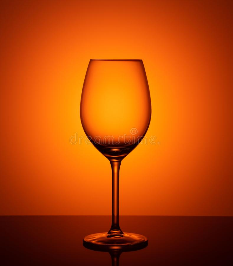 Gobelet en verre vide sur le fond orange photographie stock
