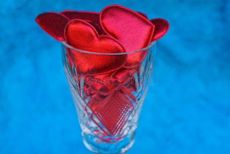 Gobelet transparent en verre complètement de coeurs rouges sur le fond bleu photo stock