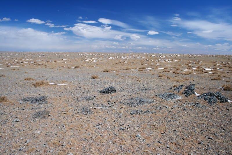 Gobi-Wüstenlandschaft mit schneebedeckten Stellen, beige Sanden und schwarzen Felsen an einem sonnigen Tag, Mongolei stockbilder