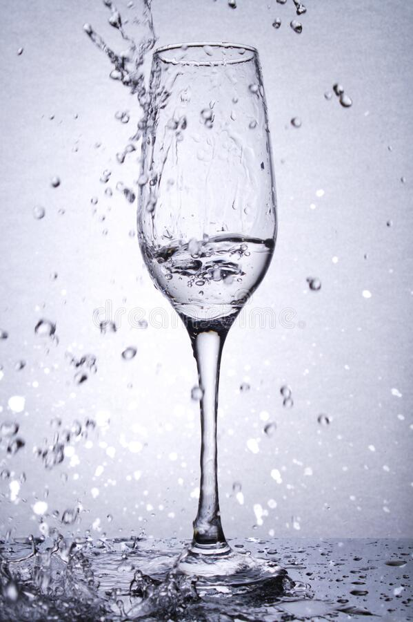 Goblet de vidro com líquido, esmaltes de água fotografia de stock
