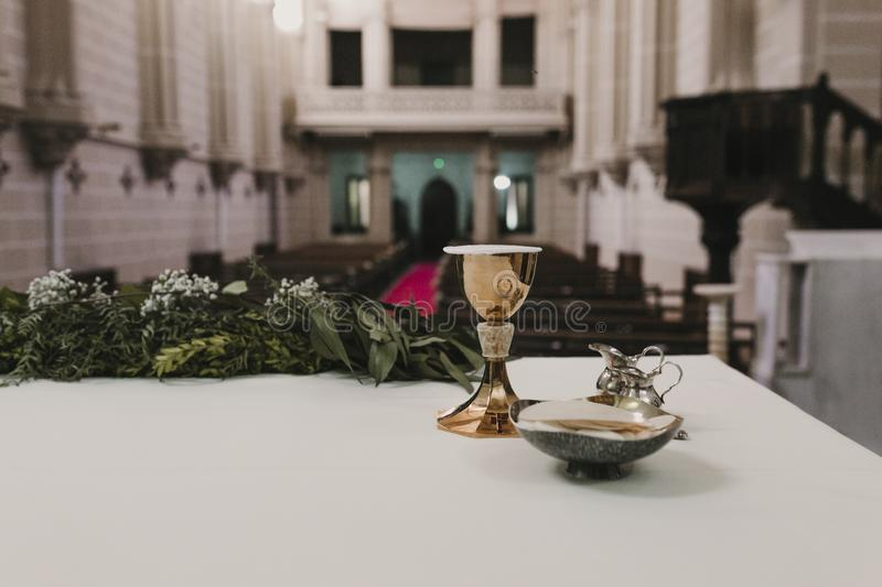 Goblet of wine on table during a wedding ceremony nuptial mass. Religion concept. Catholic eucharist ornaments for the celebration stock photo