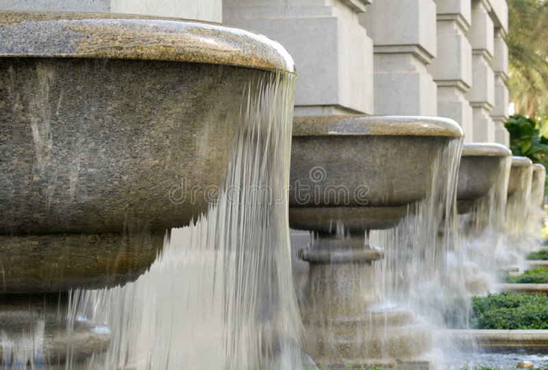 Goblets of Fountains. Fountains fashioned after giant goblets lined a columned wall in a Victorian styled grand building royalty free stock images