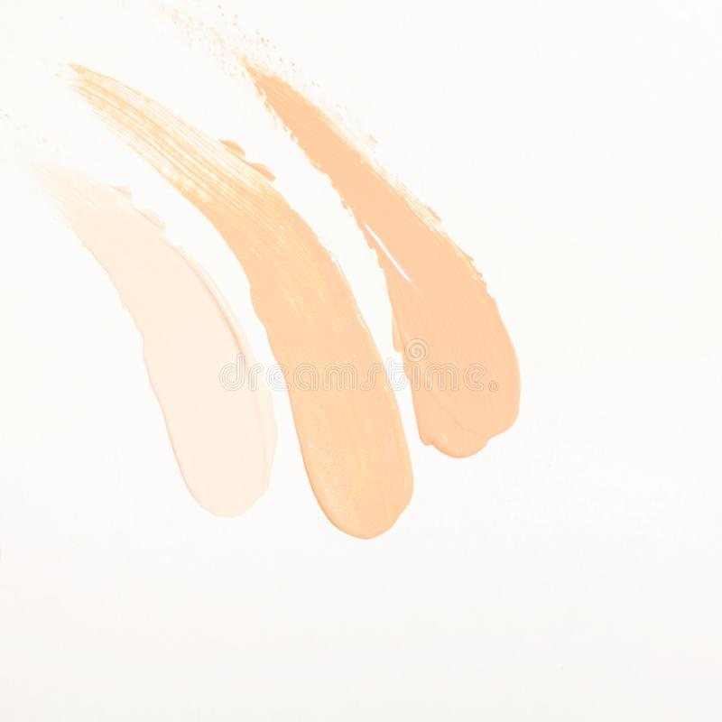 Gocce della crema di fondamento e sbavature delle tonalità differenti per i tipi differenti della pelle Estetiche e trucco fotografia stock