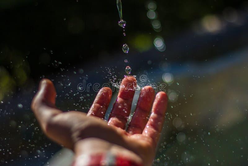 Gocce di acqua che colpiscono il dito fotografia stock libera da diritti