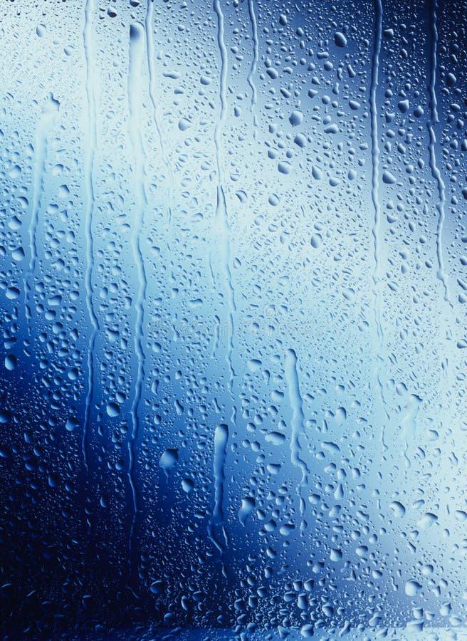 Gocce di acqua che corrono giù il vetro blu fotografia stock libera da diritti