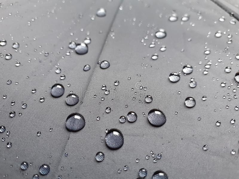 Gocce di acqua su struttura nera dell'ombrello fotografia stock libera da diritti