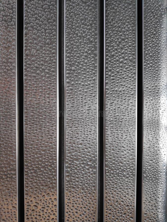 Gocce di acqua sulla superficie della sedia del metallo con poca riflessione immagine stock