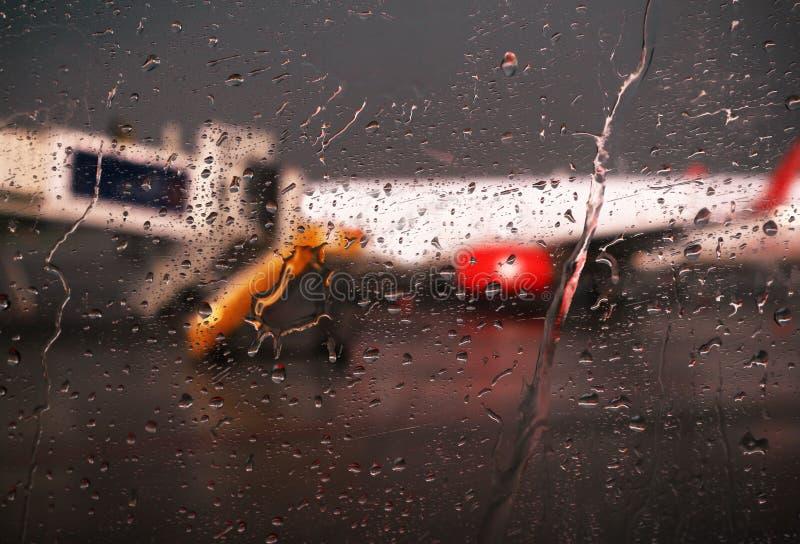 Gocce di pioggia che cadono sul vetro all'aeroporto fotografie stock