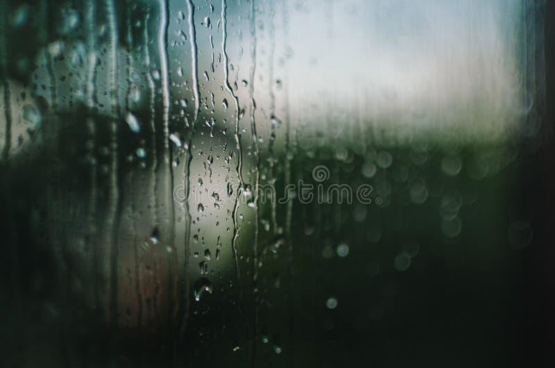 Gocce di pioggia che corrono giù una finestra fotografia stock