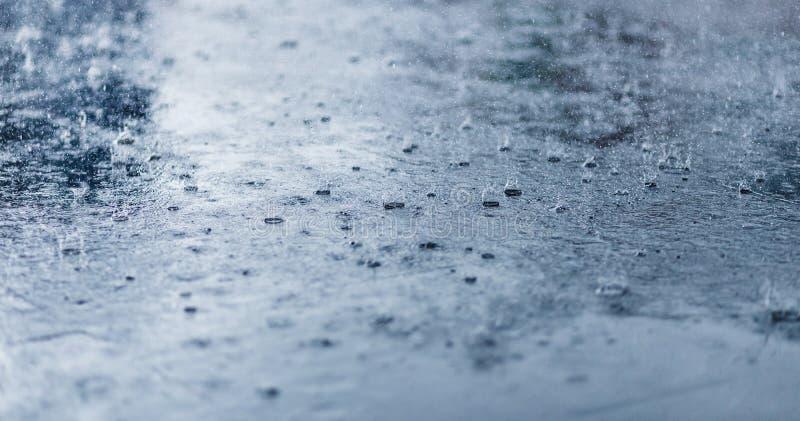 Gocce di pioggia pesanti sul primo piano dell'asfalto Tonalità fredda immagini stock libere da diritti