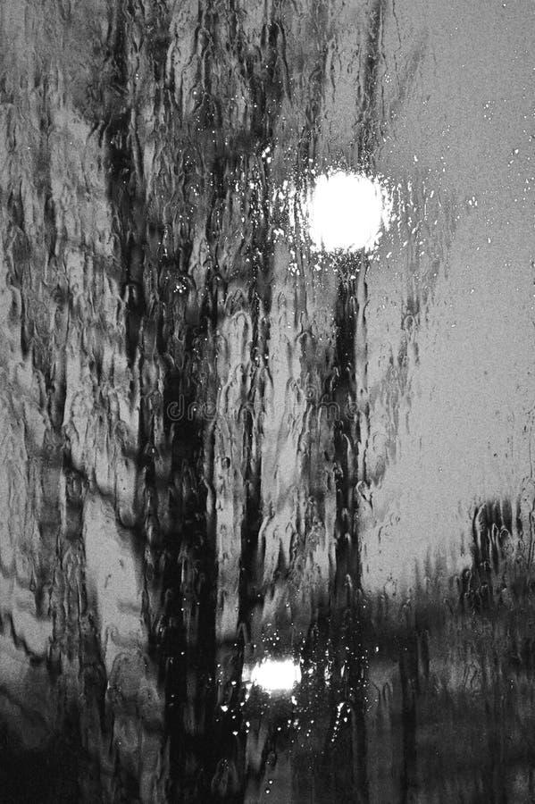 Gocce di pioggia scure di notte sulla finestra di vetro fotografie stock