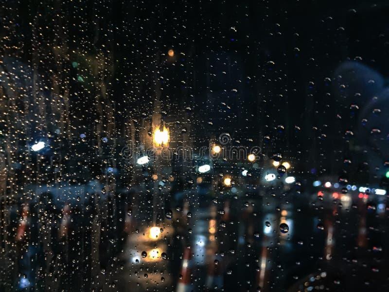 Gocce di pioggia su fondo di vetro blu alla notte, la luce dall'automobile fotografia stock libera da diritti