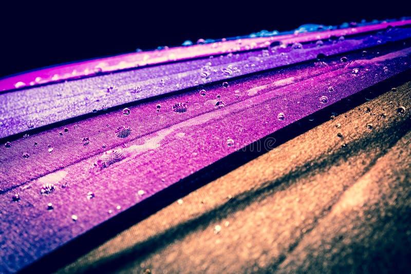 Gocce di pioggia su un ombrello variopinto con tutti i colori precedenti dei waterdrops del primo piano dell'arcobaleno di macro fotografia stock libera da diritti