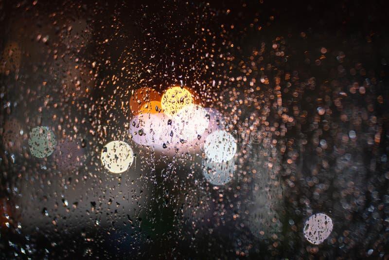Gocce di pioggia su vetro con un bello fondo vago fotografie stock