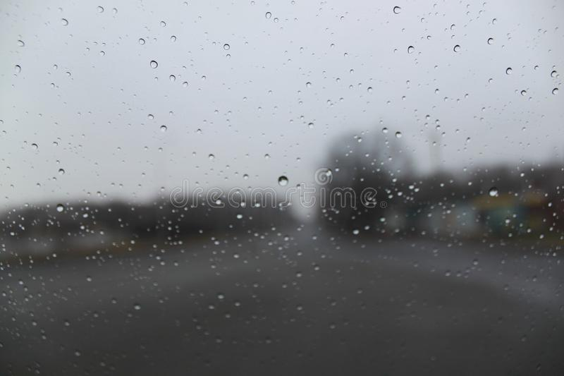 Gocce di pioggia sul primo piano di vetro Sugli alberi vaghi e sulle case di un fondo fotografia stock