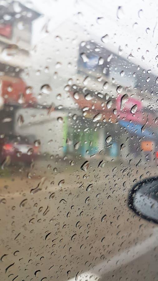 Gocce di pioggia sul vetro dell'automobile con urbano immagine stock